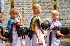 MANDALAY, MYANMAR- SEPTEMBER 26, 2016: Buddhist monks collecting alms at the temple Royalty Free Stock Images