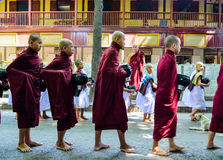 MANDALAY, MYANMAR- SEPTEMBER 26, 2016: Buddhist monks collecting alms at the temple Stock Photography