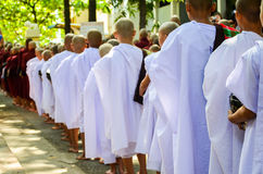 MANDALAY, MYANMAR- SEPTEMBER 26, 2016: Buddhist monks collecting alms at the temple Stock Photo
