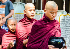 MANDALAY, MYANMAR- SEPTEMBER 26, 2016: Buddhist monks collecting alms at the temple Stock Images