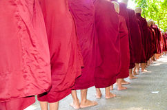 MANDALAY, MYANMAR- SEPTEMBER 26, 2016: Buddhist monks collecting alms at the temple Stock Photos