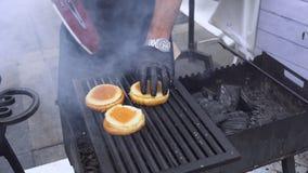 Mandanandehamburgare kock i form och handskar som lagar mat smörgåsar Trevlig ny mat och korg på gräset Kock med handskar som gri royaltyfri foto