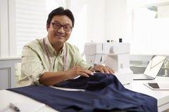 Mandanandekläder genom att använda symaskinen hemma royaltyfri bild