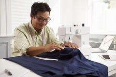 Mandanandekläder genom att använda symaskinen hemma arkivbild