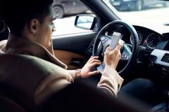 Mandando un sms nell'automobile immagini stock