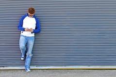 Mandando un sms sul backgropund blu-grigio Immagini Stock Libere da Diritti