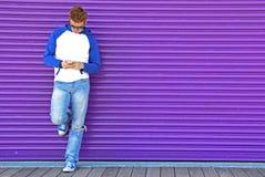 Mandando un sms sulla porpora Fotografie Stock
