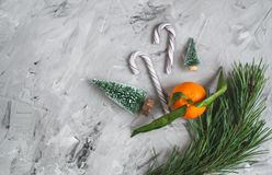 Mandarín con las hojas y las luces, naranja de la mandarina en las decoraciones del año de Gray Table Background Christmas New fotografía de archivo libre de regalías