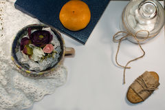 Mandarín en el libro azul y las galletas, flores Fondo blanco Fotos de archivo libres de regalías