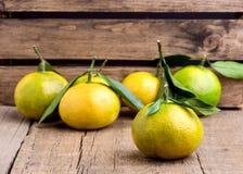 Mandarín maduro con la fruta cítrica del mandarín de la mandarina de las hojas en los agrios de madera del fondo de la tabla hori Fotos de archivo