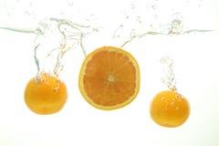 Mandarín maduro dos y chapoteo anaranjado de la rebanada del agua en blanco fotos de archivo