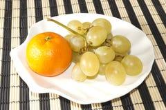 Mandarín y uvas en la placa en la forma de cáscaras Foto de archivo
