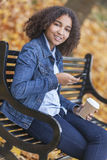 Mandare un sms afroamericano del caffè della donna dell'adolescente della corsa mista Fotografia Stock Libera da Diritti