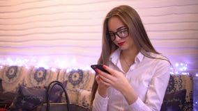 Mandare un sms felice della donna, inviante gli sms sullo smartphone in caffè 4 K Professionista femminile che utilizza app sullo video d archivio