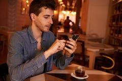 Mandare un sms millenial affascinante in un ristorante Fotografia Stock