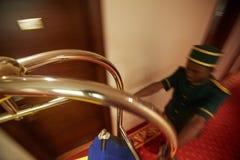 Mandarete rápido que empurra o carro da bagagem no hotel Salão imagem de stock royalty free