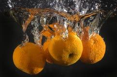 Mandarijnen die in water vallen Stock Foto