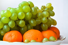 Mandarijnen en druiven die op een grote plaat liggen Royalty-vrije Stock Afbeeldingen