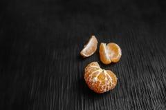 Mandarijnen op een zwarte achtergrond Veel vers fruit - mandarins Stock Afbeeldingen
