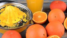Mandarijnen, sinaasappelen, een glas jus d'orange en handcitrusvrucht squezeer op blauwe houten achtergrond Sinaasappelen die in  stock footage