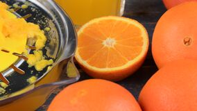 Mandarijnen, sinaasappelen, een glas jus d'orange en handcitrusvrucht squezeer op blauwe houten achtergrond Sinaasappelen die in  stock videobeelden