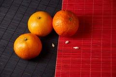 Mandarijnenmandarins, clementines, citrusvruchten op stijl zwarte en rode achtergrond met exemplaarruimte stock foto