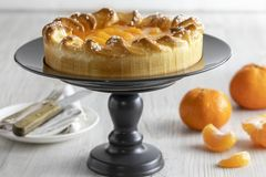 Mandarin cake and tangerines on rustic background royalty free stock photography