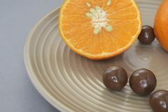 Mandarin with chocolate dragee in a beige ceramic plate royalty free stock photo