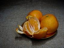 Mandarin or clementine oranges, dark still life on rustic hessian. Light painting technique. Three fruit, one part. Mandarin or clementine oranges, dark still royalty free stock images