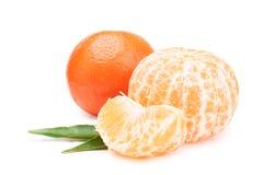 mandarin Duas tangerinas, descascadas e inteiras em um fundo branco com folhas em um fundo branco fotografia de stock