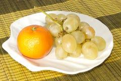 Mandarin en druiven op plaat in vorm van shells Stock Foto