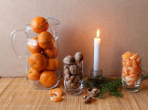 Mandarin fruit nuts filbert. Mandarin fruit nuts pitcher wineglass glass filbert candle candlestick mat grass fruit vitamins royalty free stock images