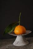 Mandarin on a gray vintage bowl. On a gray stone background stock photos