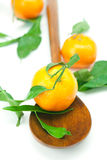 Mandarin with green leaves on a wooden spoon Royalty Free Stock Photo
