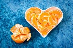Mandarin i en vit platta i formen av en hjärta royaltyfria foton