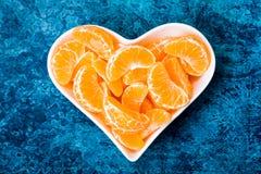 Mandarin i en vit platta i formen av en hjärta arkivbilder
