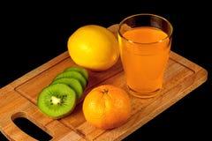Mandarin, kiwi, lemon and glass of juice Stock Photos