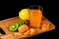 Mandarin, kiwi, lemon and glass of juice on a black background Stock Image