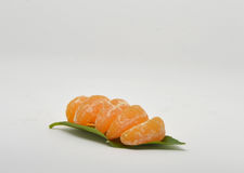 Mandarin with leaves close-up on a white. Ripe mandarin with leaves close-up on a white background. Tangerine orange with leaves on a white background Royalty Free Stock Photography