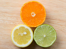 Mandarin, lemon, and green lime slices on wooden background Royalty Free Stock Photo