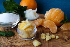 Mandarin lip and body scrub. Mandarin orange lip and body scrub, coconut oil, sugar, and mint leaves on a beautiful olive wood board Royalty Free Stock Photography