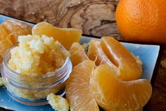 Mandarin lip and body scrub. Mandarin orange lip and body scrub and mint leaves on a beautiful olive wood board Stock Photo