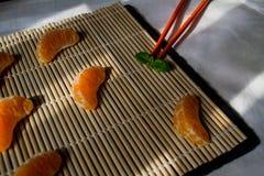 Mandarin of mandarijn met eetstokjes als sushi stock foto's