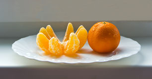 The mandarin and the mandarin slices on the plate Stock Photo