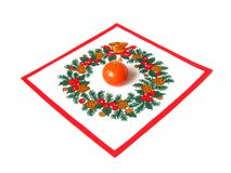 Mandarin on the napkin. One mandarin on the napkin with christmas pattern isolated Royalty Free Stock Images