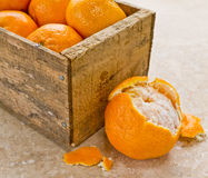 Mandarin Orange or Clementines. A wooden box full of fresh citrus mandarin oranges or clementines with one half opened orange royalty free stock photo