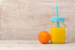Mandarin orange juice in mason jar and fruit over wooden background with copy space. Healthy eating or dieting Royalty Free Stock Photos