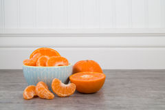 Mandarin orange slices in a blue bowl on a wooden table Stock Photos