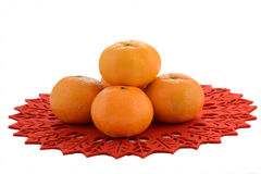 Mandarin oranges. Fresh mandarin oranges on festive poinsettia mat isolated on white background with room for text Royalty Free Stock Photography