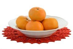 Mandarin oranges. Fresh mandarin oranges on festive poinsettia mat isolated on white background with room for text Stock Photography